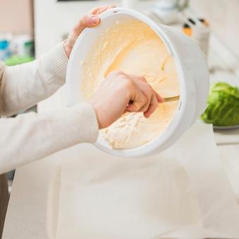 Colheita de mãos colocando massa em panela de cerâmica