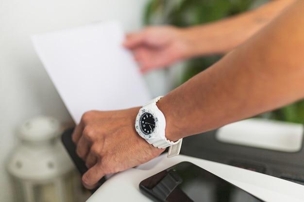 Colheita de mãos colocando papel na impressora