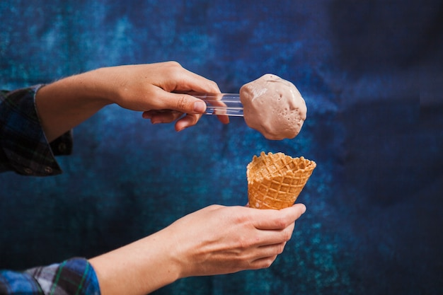 Colheita de mãos colocando sorvete no cone