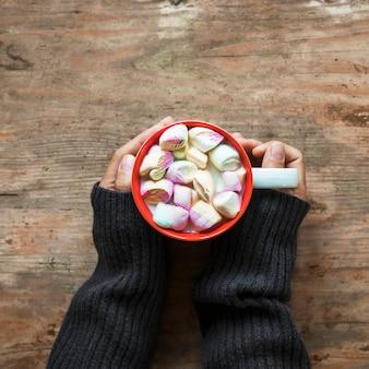 Colheita de mãos com caneca de chocolate quente