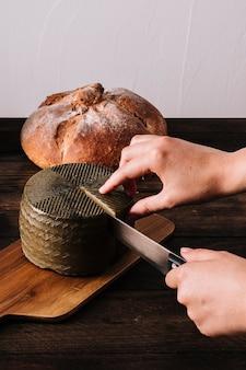 Colheita de mãos cortar queijo perto de pão