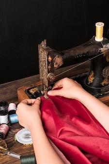 Colheita de mãos costurando vestuário vermelho na máquina