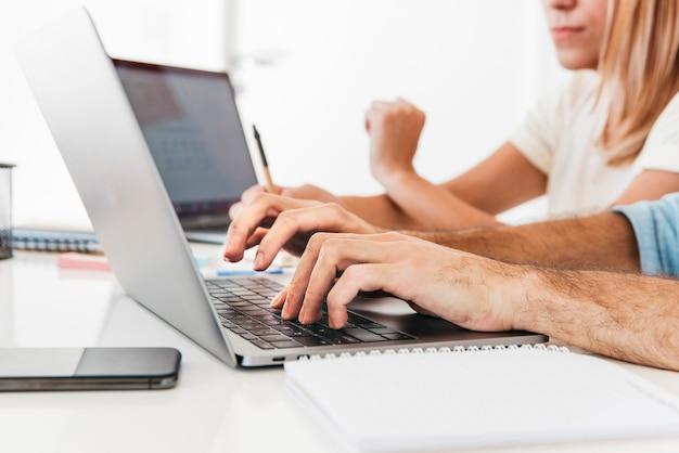 Colheita de mãos digitando no laptop no local de trabalho