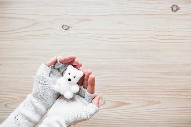 Colheita de mãos em luvas segurando urso branco