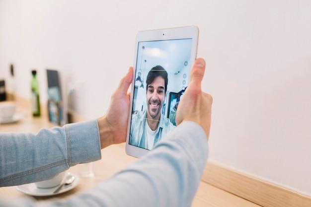 Colheita de mãos masculinas tomando selfie com tablet