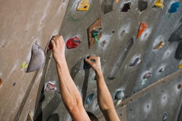 Colheita de mãos na parede de escalada