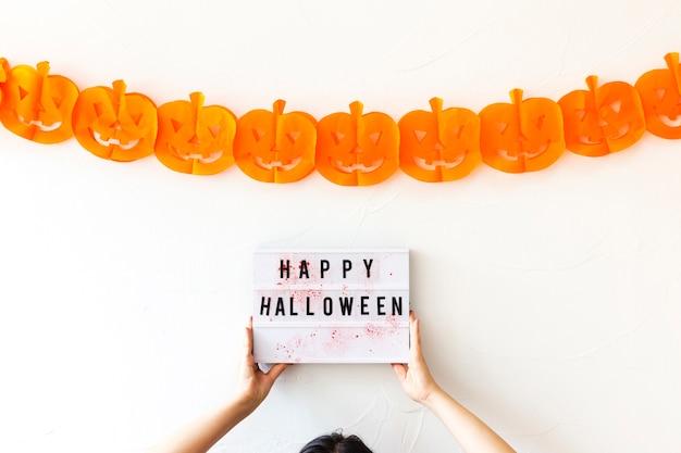 Colheita de mãos segurando a placa com a escrita perto de guirlanda de halloween