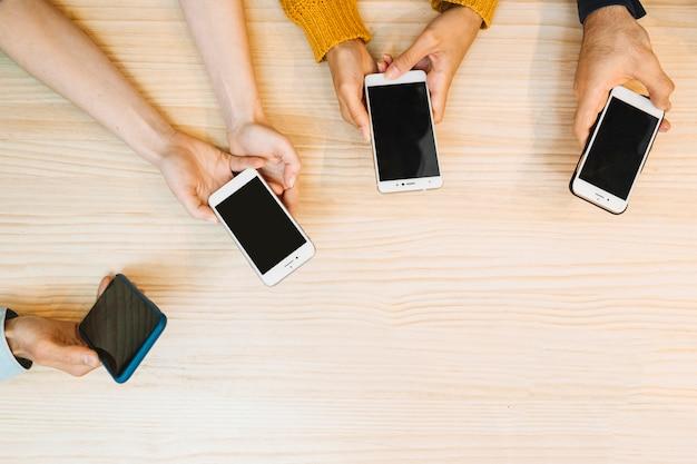 Colheita de mãos segurando e usando telefones celulares
