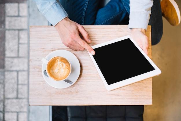 Colheita de mãos segurando o tablet com café nas proximidades