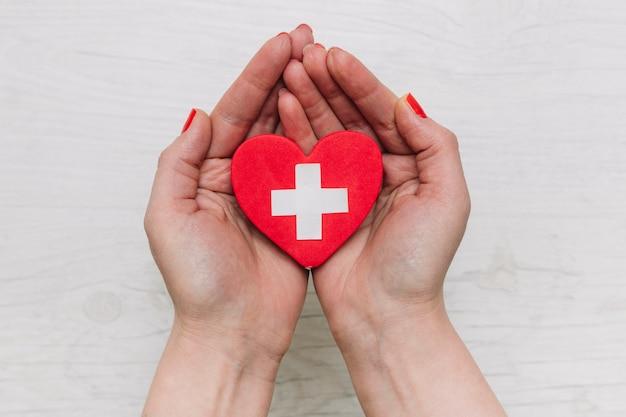 Colheita de mãos segurando um coração com cruz