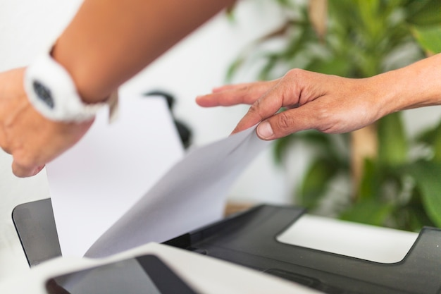 Colheita de mãos tomando papel da impressora
