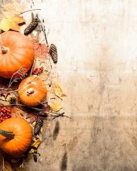 Colheita de outono. abóbora madura com folhas. em fundo de madeira.