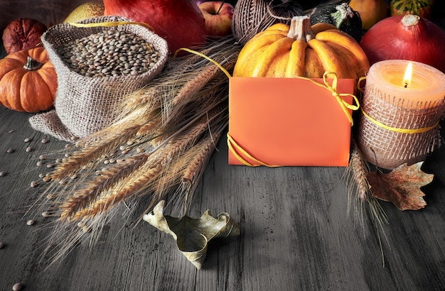 Colheita de outono ainda vida com abóboras, espigas de trigo e lentilhas no saco em madeira rústica desbotada, espaço de texto em cartão de papel