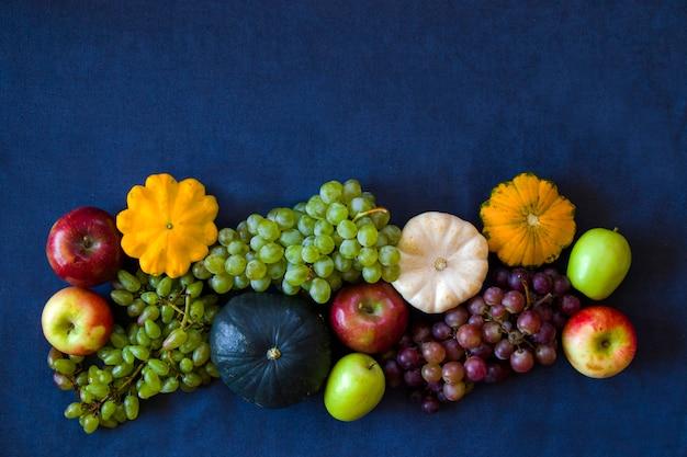 Colheita de outono e outono, abóbora, maçã, uva e patisson na mesa azul
