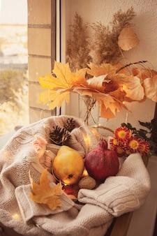 Colheita de outono: pêra, romã, nozes, folhas de outono, flores de aster em um suéter de lã.