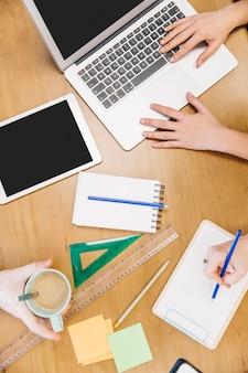 Colheita de pessoas trabalhando na mesa com o laptop