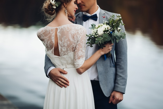 Colheita de recém-casados elegantes perto do lago