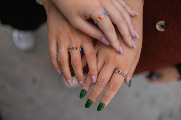 Colheita de três garotas mostrando sua manicure estilosa segurando os dedos em uma bolsa de couro preto ...