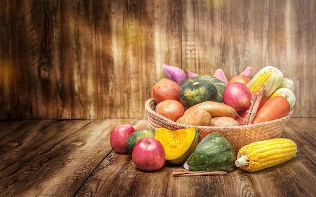 Colheita de vegetais de férias de outono em uma cesta com fundo de madeira
