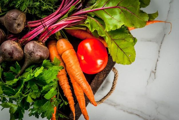 Colheita de verão, outono. legumes de fazenda orgânica fresca em uma caixa de madeira em uma beterraba de mesa de mármore branca, cenoura, salsa, tomate. vista do topo