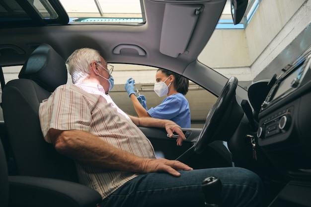 Colheita enfermeira enchendo seringa com vacina contra motorista em carro