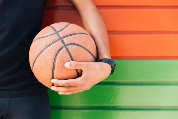 Colheita étnica homem segurando basquete