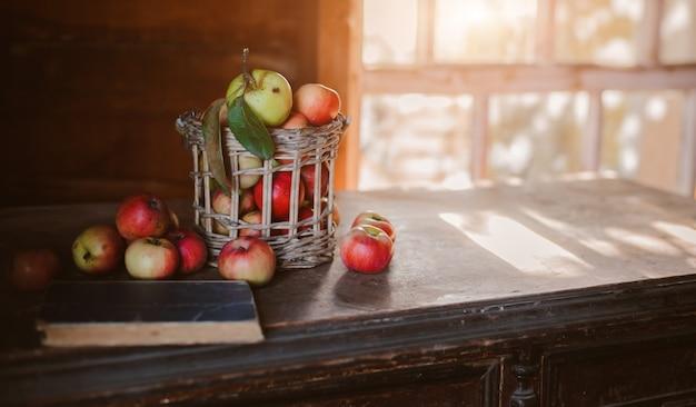 Colheita fresca de maçãs maduras e saudáveis da fazenda em uma jarra de vidro, em uma cesta.