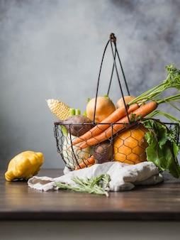 Colheita fresca dos vegetais, dos nabos, das cenouras, da erva-doce, da abóbora, do pattinson e do milho na cesta de fio do metal para cozinhar o jantar.