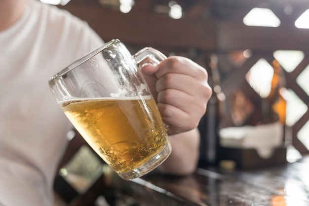 Colheita homem com cerveja encostada na mesa
