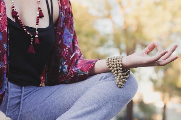 Colheita jovem mulher meditando no parque