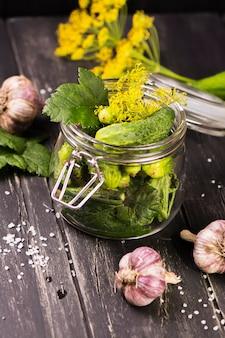 Colheita rica dos pepinos orgânicos frescos prontos para conservar em um frasco de vidro.
