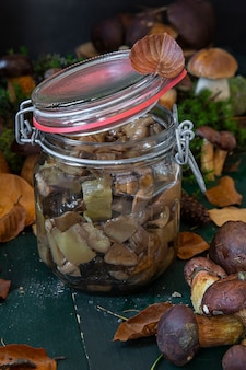 Colheita sazonal de cogumelos. preparativos para o inverno, fazendo marinadas caseiras. cogumelos marinados em uma jarra de vidro em pé sobre uma mesa de madeira com cogumelos.