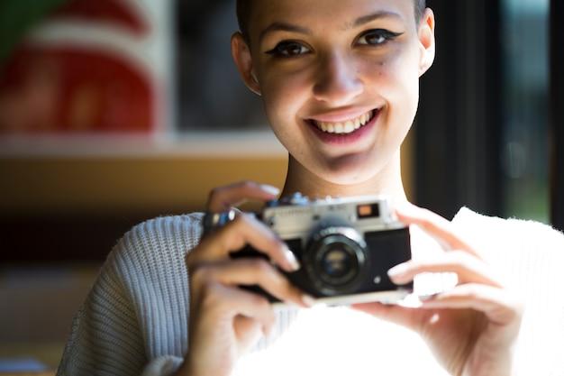 Colheita sorridente fotógrafo feminino com câmera vintage