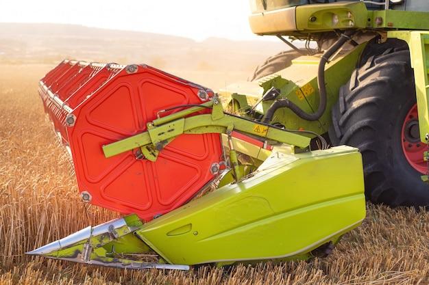 Colheitadeira close-up. colheitadeira de colheita de trigo ao pôr do sol.