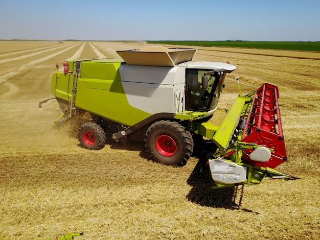 Colheitadeira no campo de trigo com palha de poeira no ar.