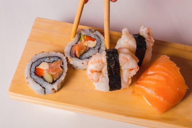 Colhendo à mão rolos de sushi e sashimi em uma placa de madeira usando os pauzinhos.