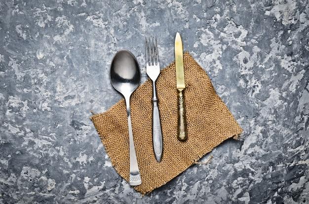 Colher antiga, garfo, faca em um guardanapo deite sobre uma mesa de concreta cinza. vista do topo.