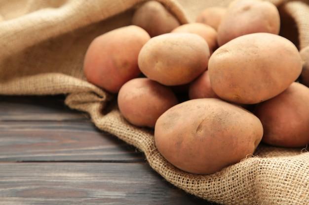 Colher as batatas em um saco de estopa em fundo rústico com espaço de cópia