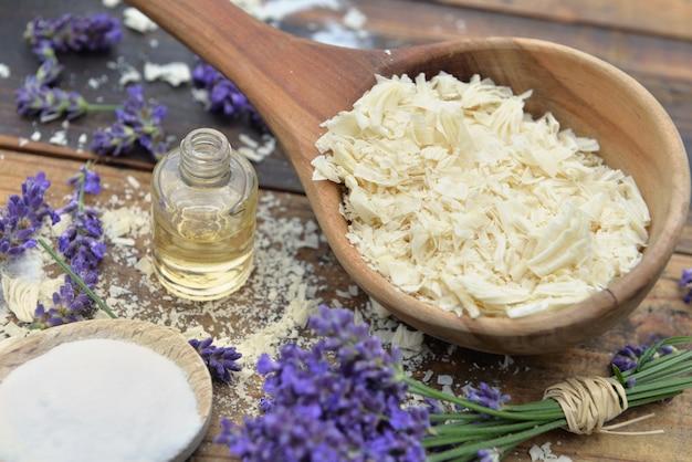 Colher cheia de flocos de sabão com óleo essencial e monte od flores de lavanda e bicarbonato de sódio em fundo de madeira