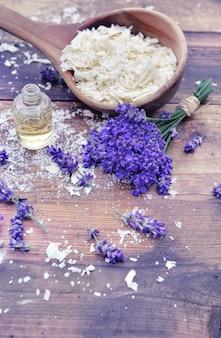Colher cheia de flocos de sabão com óleo essencial e monte od flores de lavanda em fundo de madeira