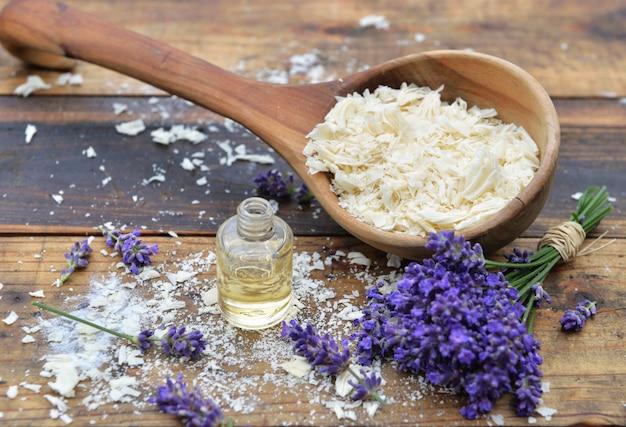 Colher cheia de flocos de sabão com óleo essencial e ramo de flores de lavanda na mesa de madeira
