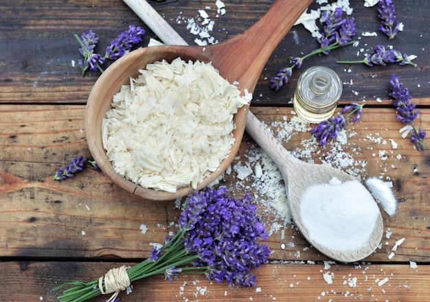 Colher cheia de flocos de sabão com óleo essencial e ramo de lavanda com bicarbonato em fundo de madeira