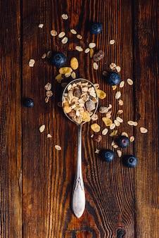 Colher cheia de granola e mirtilo na mesa de madeira. vista de cima