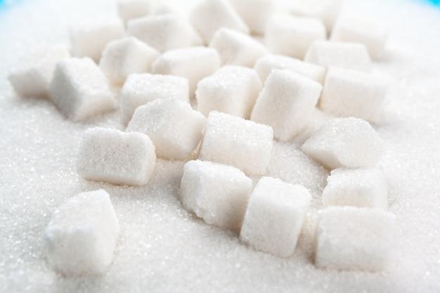 Colher com areia branca e açúcar em pedaços