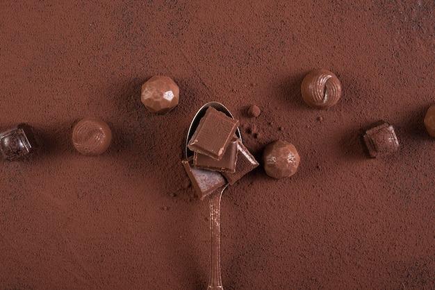 Colher com barra de chocolate quadrados doces e cacau em pó
