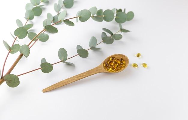 Colher com cápsulas de vitamina d em fundo branco com eucalipto