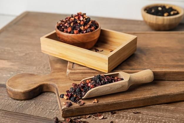Colher com chá de frutas secas na superfície de madeira