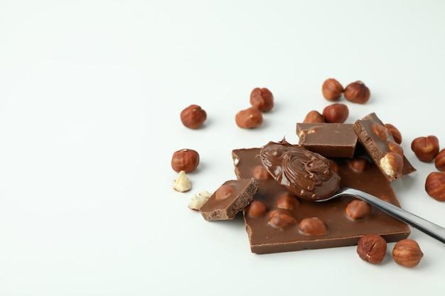 Colher com pasta de chocolate e chocolate com nozes no fundo branco