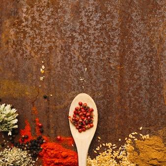 Colher com pimenta rosa perto de especiarias