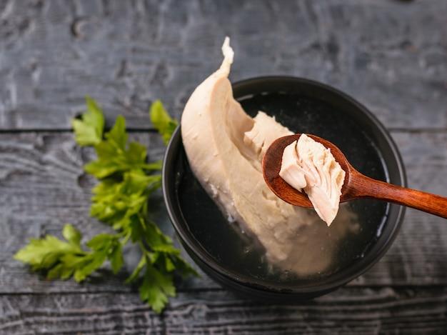 Colher com um pedaço de peito de frango cozido e uma tigela de carne e caldo de carne na mesa de madeira.